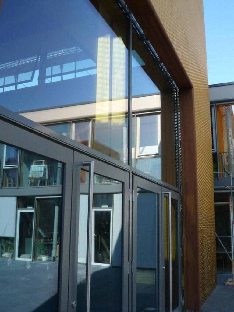 Fenster der Joha spiegeln Gemeindehaus und Kita
