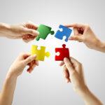 Puzzle-Teile werden in Teamarbeit zusammengesetzt