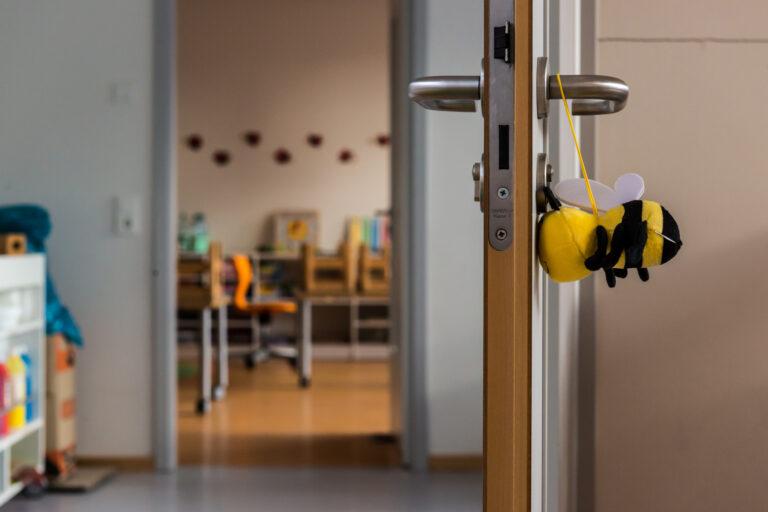 Blick in die Kita durch eine geöffnete Tür, an deren Türgriff eine Plüsch-Biene hängt