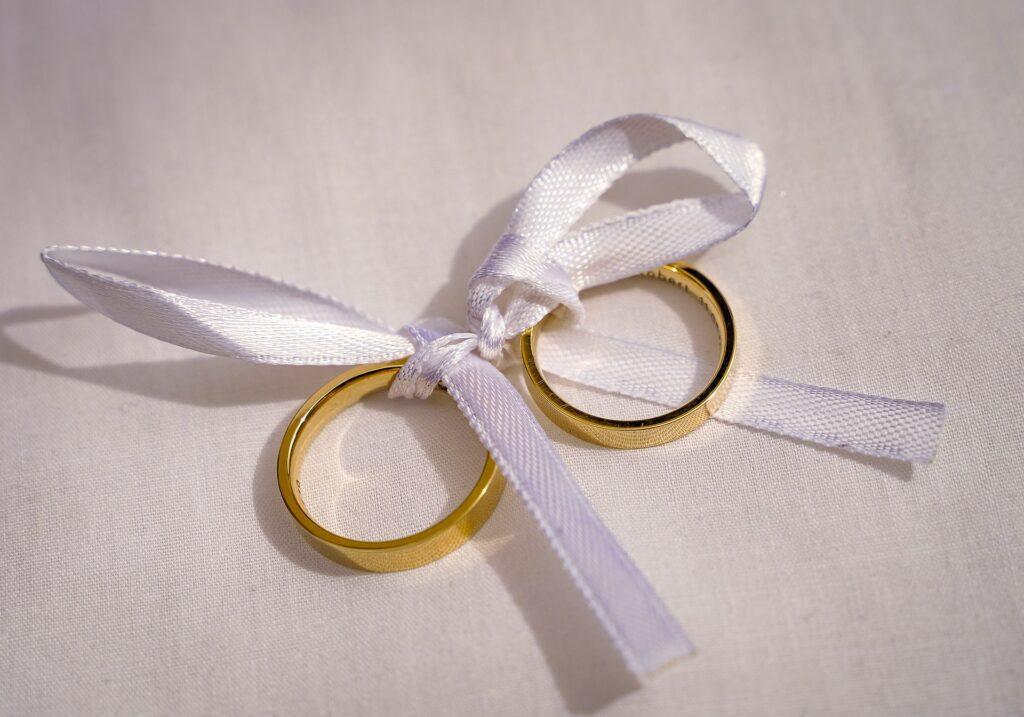 Zwei mit einer weißen Schleife verbundene goldene Ringe