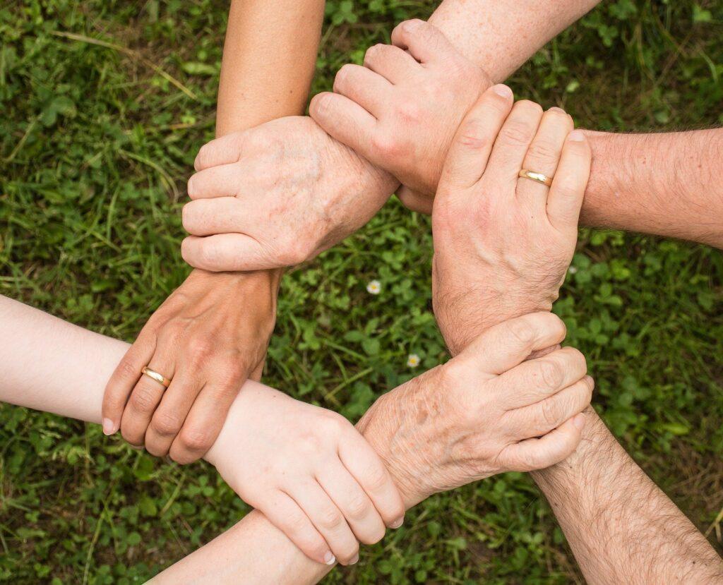 sechs Hände halten reihum das Handgelenk der vorhergehenden