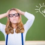 Mädchen geht beim Nachdenken vor einer Tafel ein Licht auf