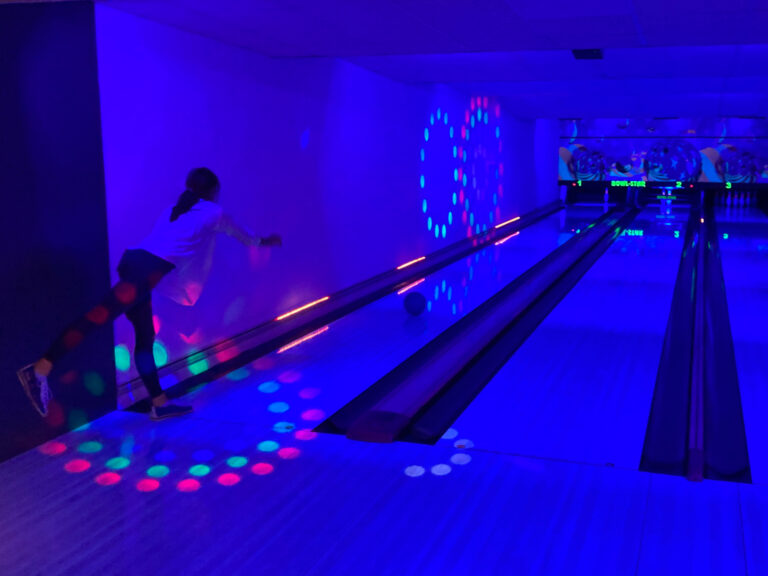 ehemalige Konfirmandin versucht den letzten Pin beim Schwarzlicht-Bowling zu treffen